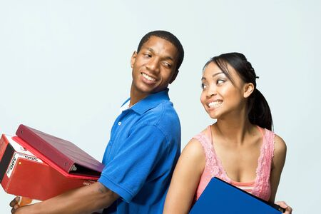 Two teenagers standing back to back holding notebooks are smiling as they look at each other. Horizontally framed photograph photo