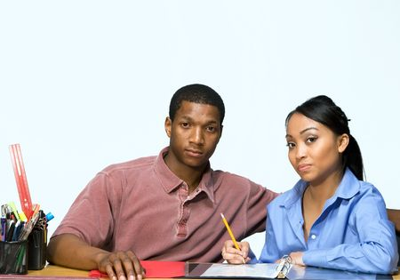 Two Teens are are seated at a desk taking notes and looking serious. There are pencils, folders, and paper on the desk. Horizontally framed photgraph photo