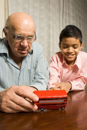 Grandfather and grandson are sitting at the table while grandfather inspects the toy bus with his glasses on. Grandson sits beside him watching happily. This is a vertically framed photo.
