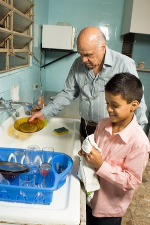 Grandfather and grandson stand together washing dishes. Grandson wipes down a utensil as grandfather washes a plate. This is a vertically framed photo. Stock Photo