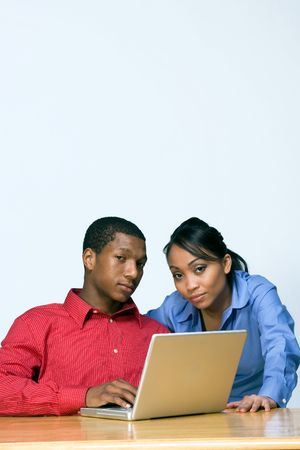 Two Teens looking serious as they stare ahead and he holds a Laptop Computer. Vertically framed photograph photo