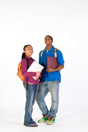 vertically: Two students stand and look at  the camera with happy expressions on their faces. They wear backpacks and he carries a notebook. Vertically framed photograph.