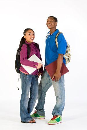 sch�ler: Zwei Studenten stehen und schauen in die Kamera mit gl�cklichen Ausdr�cke in ihren Gesichtern. Sie tragen Rucks�cke und er tr�gt ein Notebook. Vertikal gerahmte Fotografie.  Lizenzfreie Bilder