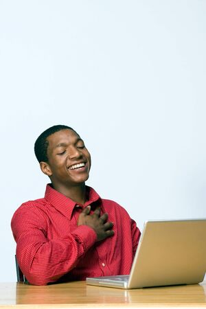 he laughs: Male teen student laughs while he looks at his laptop computer. Vertically framed photograph Stock Photo