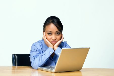 Female student appears sad and frustrated as she works on her laptop. Horizontally framed photograph. Stock Photo