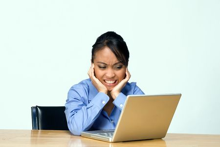 frowns: Female student appears mad and frustrated as she frowns at her laptop. Horizontally framed photograph. Stock Photo