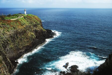 Lighthouse perched upon a large vegetation covered cliff overlooking an endless sea. Banco de Imagens