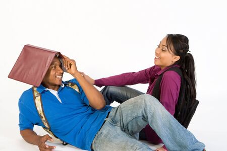 studious: Studious, attractive teen couple flirting.  The young man is lounging on the ground with a folder on his head.  The young woman, who is sitting on the ground, is looking at him laughing.