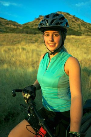 mountainbike: Attractive smiling female mountain-biker, wearing full cycle gear, straddling a mountain-bike in front of a beautiful hill and afternoon sky.  Vertically framed shot. Stock Photo