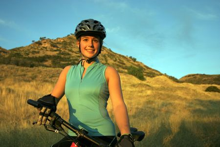 mountainbike: Attractive smiling female mountain-biker, wearing full cycle gear, straddling a mountain-bike looking off into the distance.  Horizontally framed shot on with golden grasses and a blue sky in the background. Stock Photo