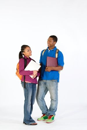 Two students stand and look at  each other with happy expressions on their faces. They wear backpacks and he carries a notebook. Vertically framed photograph.