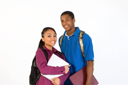 Two students stand and look at the camera while smiling. They wear backpacks and he carries a notebook. Horizontally framed photograph.