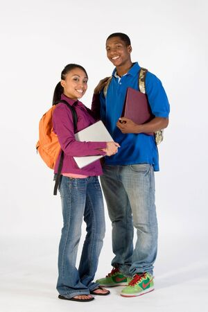 Two students stand and look at  the camera while smiling. They wear backpacks and he carries a notebook. Vertically framed photograph.