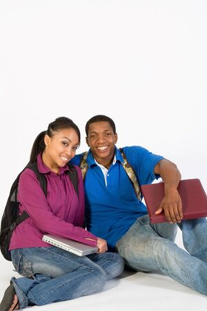 Two seated students are sitting on the ground smiling. Both wear backpacks and he carries a notebook. Vertically framed photograph Stock Photo - 3212915