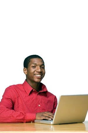 Male teen student smiles at the camera as he works on his laptop computer. Vertically framed photograph