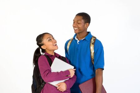 Two students stand and look at each other while laughing. They wear backpacks and he carries a notebook. Horizontally framed photograph. Stock Photo - 3212864