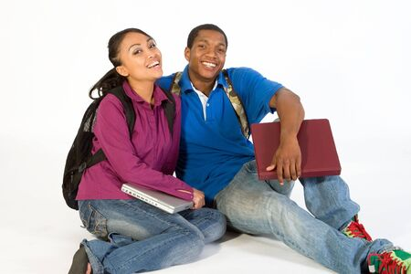 Two Students are sitting on the ground smiling at the camera. Both wear backpacks and he carries a notebook. Horizontally framed photograph Stock Photo - 3212916