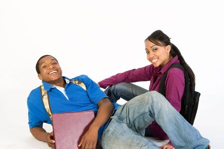 Two Students are sitting on the ground smiling at the camera. Both wear backpacks and he carries a notebook. Horizontally framed photograph Stock Photo - 3212917