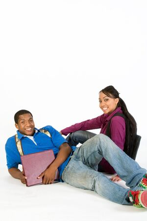 Two Students are sitting on the ground smiling at the camera. Both wear backpacks and he carries a notebook. Vertically framed photograph Stock Photo - 3212881