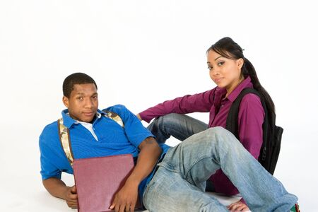 Studious, attractive teen couple wearing backpacks and holding books lying on the ground.