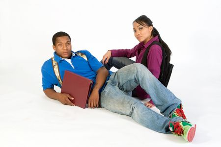 bore: Two students seated on the ground wearing serious expressions and backpacks. Horizontally framed photograph