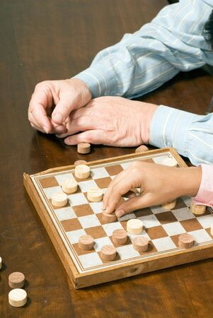 Close-up shot of a grandfather's and grandson's hands playing checkers.