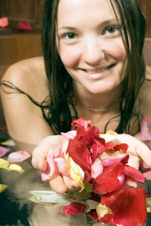 Woman smiles as she scoops up flower petals in her hands while she bathes. Vertically framed photograph.