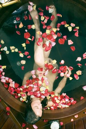 vertically: Aerial View of woman in tub surrounded by flowers. Vertically framed photograph.