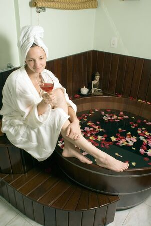 red bathrobe: Woman in bathrobe relaxes by a spa tub filled with rose petals as she sips a glass of red wine. Vertically framed photograph