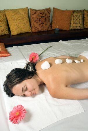 as: Woman closes her eyes and relaxes as she gets a hot stone massage. Vertically framed photograph.
