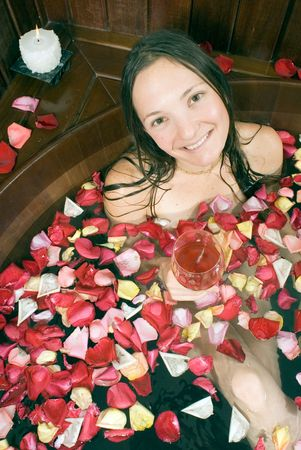 soaks: Woman smiling as she soaks with flower petals in a tub. Vertically framed photograph. Stock Photo