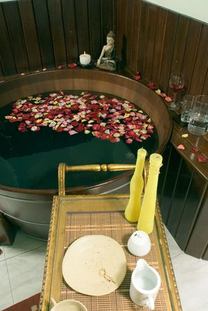 Picture of a spa room with a tub filled with flower petals. There are candles, water, wine and a statue. Vertically framed photograph