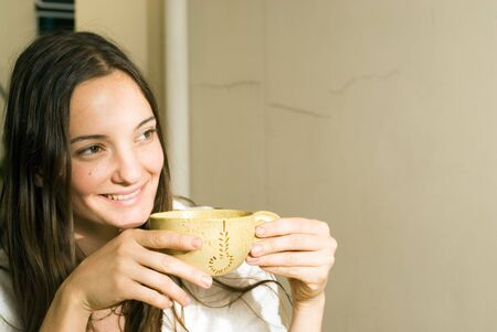 Woman holding a tea cup smiles as she looks away. Horizontally framed photograph.