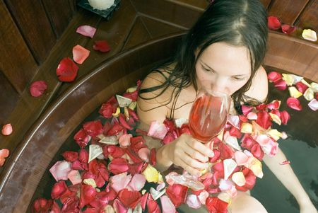 Woman relaxes in a spa tub filled with flowers sips red wine. Horizontally framed photograph Imagens