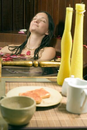 vertically: Woman relaxes in a spa tub filled with rose petals. She is closing her eyes and looks happy and relaxed. There are candles and lunch in the foreground. Vertically framed photograph Stock Photo