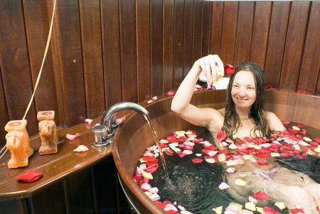Une belle jeune fille assise dans une baignoire pleine d'eau. P�tales de rose flottant dans baignoire tandis que l'eau est en cours d'ex�cution. Horizontalement dans le cadre photo.  Banque d'images - 3222788