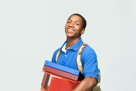 Happy male student wearing a backpack carries notebooks and boxes. Horizontally framed photograph. Stockfoto