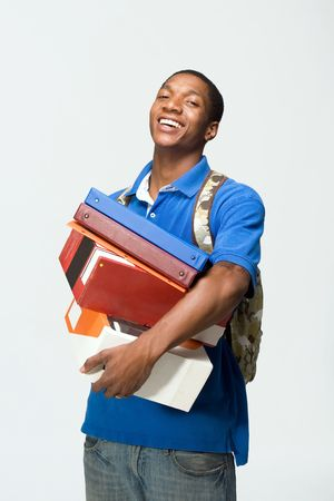 vertically: Male student wearing a backpack carries notebooks and boxes.  He is laughing. Vertically framed photograph.