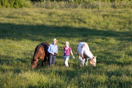 Twee boeren lachend voor de camera, terwijl in een groen gebied van gras, terwijl hun paarden eten. - Horizontaal omlijst