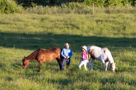 Twee boeren praten in een groen gebied van gras, terwijl hun paarden eten. - Horizontaal omlijst