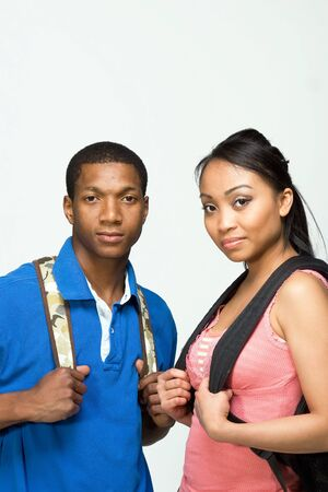 study group: Two students wearing backpacks look at the camera and smile. Vertically framed photograph