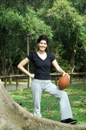 Young, attractive woman is posing next to a tree.  She is smiling and holding a football.   Vertically framed shot photo