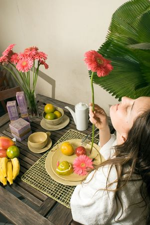 An attractive young girl, smelling a pink flower, sitting at a table, while fruits and plants surround her. - vertically framed