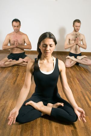 A woman and two men meditate while on hardwood floor. - vertically framed photo