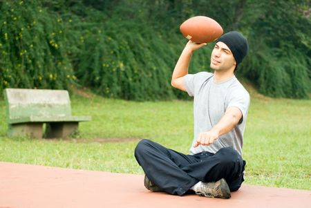 A man, sitting on the park ground, throwing a football, smiling - horizontally framed photo