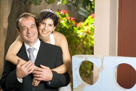 Hoewel nog steeds op hun bruiloft kleren, een pas getrouwde vrouw hugs haar pas getrouwde man. - Horizontaal omlijst