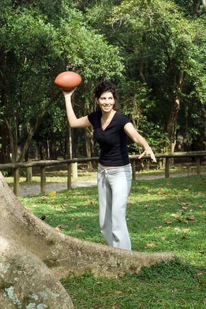 A young, attractive woman is standing next to a tree at the park.  She is smiling and about to throw a football.Vertically framed photo. photo