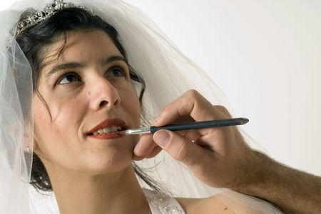 A woman getting a red shade of lip liner on her lips. She is preparing to get married. - horizontally framed