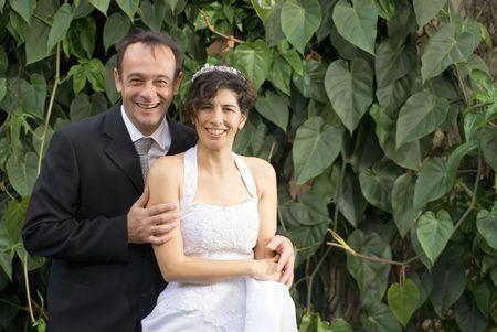 Een pas getrouwd paar glimlach op de camera, terwijl in hun huwelijk kleren. - Horizontaal omlijst