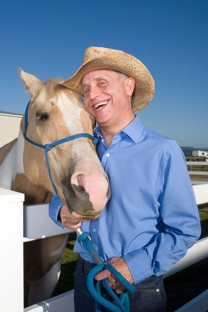 he laughs: Cowboy laughs as he poses with his spotted horse next to a fence. Vertically framed photograph. Stock Photo
